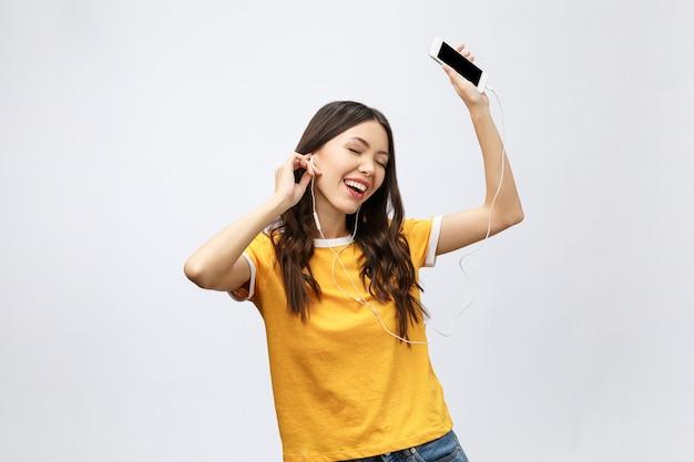 Linda garota asiática com maquiagem profissional e penteado estiloso cantando e dançando enquanto ouve música