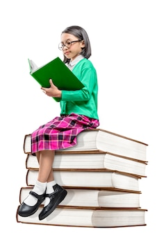 Linda garota asiática com óculos, sentado na pilha de livros e ler o livro