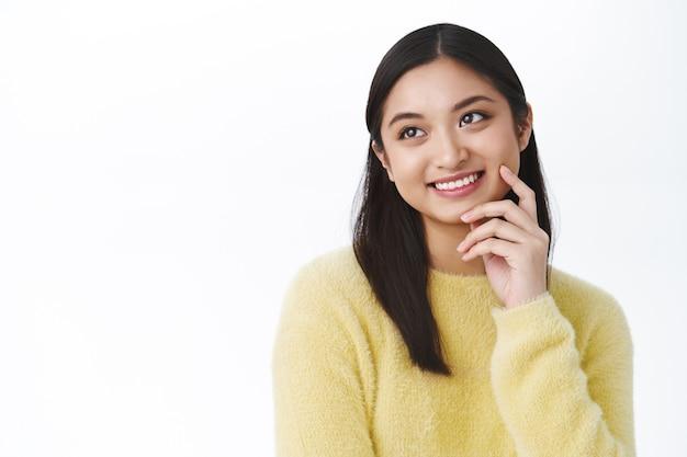 Linda garota asiática com suéter amarelo, tocando a pele limpa e brilhante, olhando para a esquerda e sorrindo feliz, usando produtos de rotina para a pele, aproveite o uso de maquiagem coreana