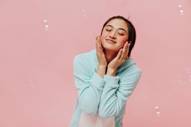 Linda garota asiática com tapa-olhos estética, sorrindo, tocando suavemente o rosto e fazendo poses com os olhos fechados na parede rosa com bolhas