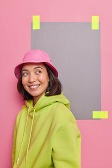 Linda garota asiática com uma expressão alegre e pensativa parece sonhadora em algum lugar, tem um sorriso feliz no rosto, usa panamá e um moletom verde posa de lado contra o espaço em branco da parede rosa