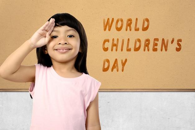 Linda garota asiática com uma expressão engraçada em pé com o texto do dia mundial da criança na parede. dia mundial da criança