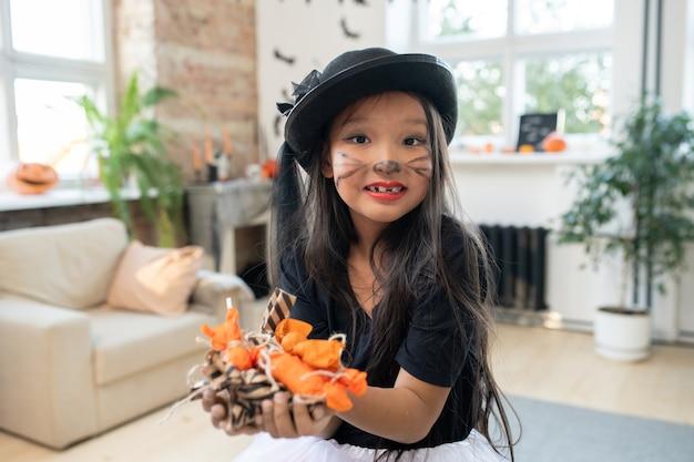 Linda garota asiática com uma pilha de doces nas mãos