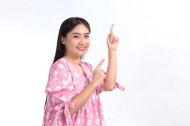 Linda garota asiática com vestido rosa age de forma emocionante e aponta para apresentar algo sobre fundo branco.