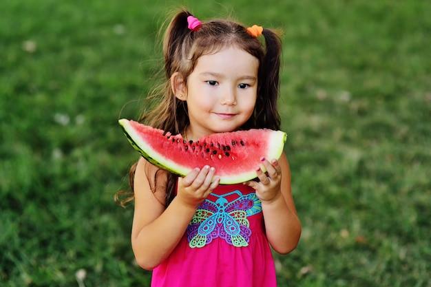 Linda garota asiática comendo melancia suculenta e sorrindo