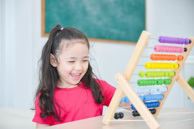 Linda garota asiática contando lenha no ábaco na escola