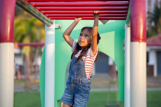 Linda garota asiática criança pendurar a barra por sua mão para exercer no recreio