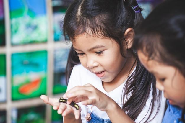 Linda garota asiática criança segurando e brincando com lagarta preta com curioso e divertido