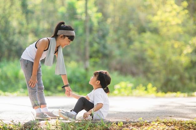 Linda garota asiática dá a mão para ajudar a irmã no acidente durante a corrida