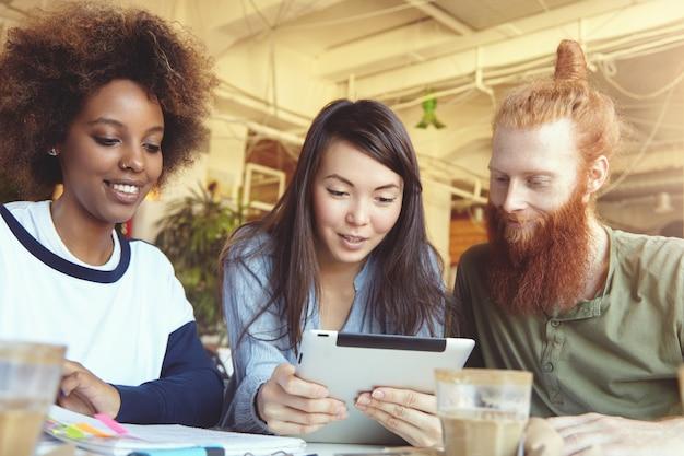 Linda garota asiática de camisa azul, segurando o tablet mostrando a apresentação para os parceiros que estão olhando para a tela com uma expressão alegre.