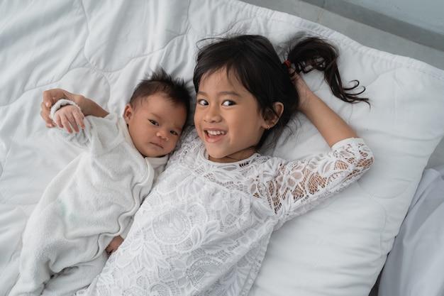 Linda garota asiática deitada na cama com seu irmãozinho