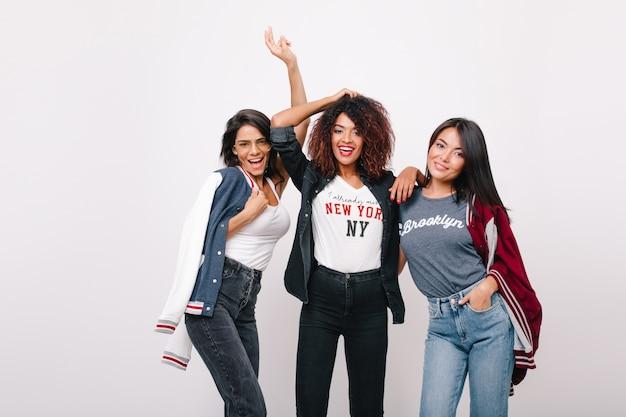 Linda garota asiática em calças jeans azul em pé perto de um amigo mulato atraente. modelo feminino latino encantador posando com colegas de universidade e se divertindo.