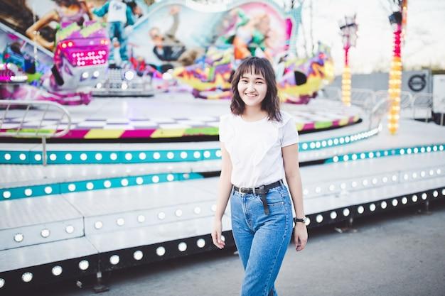 Linda garota asiática em um parque de diversões