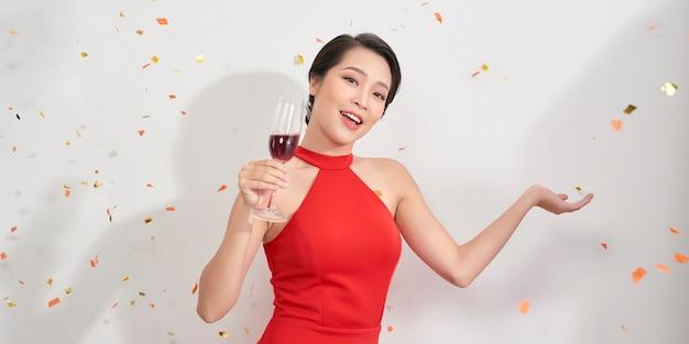 Linda garota asiática em vestido de noite, sorrindo, segurando a taça de champanhe no fundo branco.