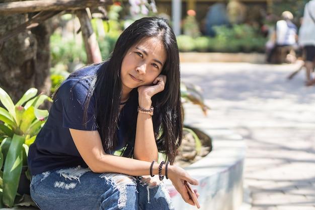 Linda garota asiática escorar e pensativo é algo e mão direita segurar smartphone