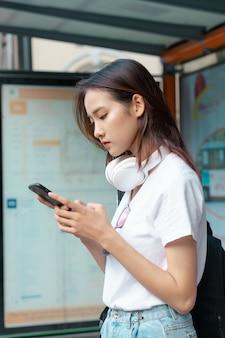 Linda garota asiática estava usando seu telefone enquanto esperava o ônibus
