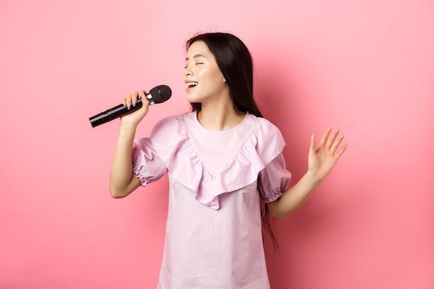 Linda garota asiática executar música, cantando no microfone e sorrindo romântico, em pé no vestido contra o fundo rosa.