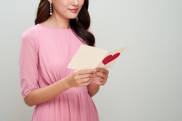 Linda garota asiática lê carta de amor. feliz dia da mulher.