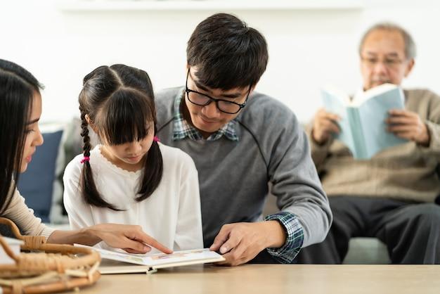 Linda garota asiática lendo um livro de desenho animado com a mãe e o pai na sala de estar