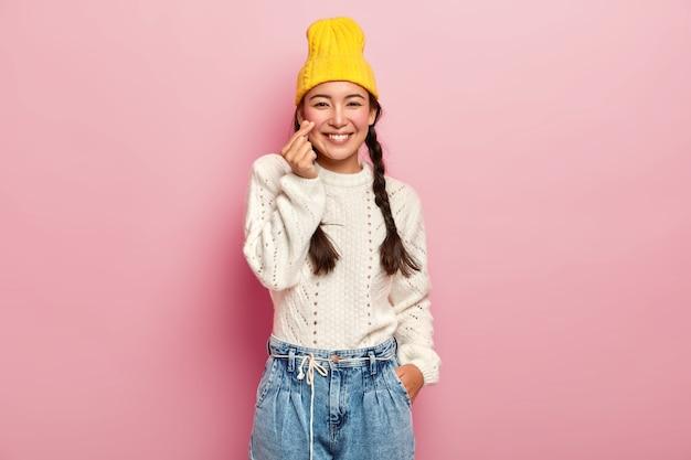 Linda garota asiática mantém os dedos dobrados em forma de coração, mostra o sinal do amor coreano, usa um elegante chapéu amarelo, suéter branco e jeans, tem cabelo escuro penteado em duas tranças, posa contra a parede rosa