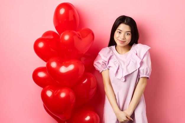 Linda garota asiática num vestido parecendo tímido e sorridente, em pé modesto perto de balões do dia dos namorados, corando em um encontro romântico, olhando para a câmera, fundo rosa.
