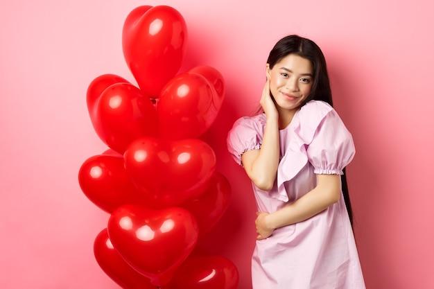 Linda garota asiática num vestido sorrindo coquete, flertando no dia dos namorados, olhando sensual para a câmera, posando perto de balões de coração do dia dos namorados, fundo rosa.
