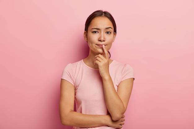 Linda garota asiática pensativa pensa em algo, toma decisões, pondera sobre ações futuras, vestida com roupa casual, tem aparência específica