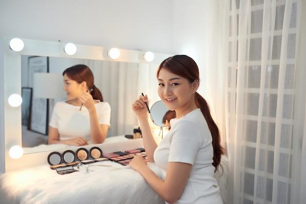 Linda garota asiática se olhando no espelho e aplicando cosméticos com um pincel