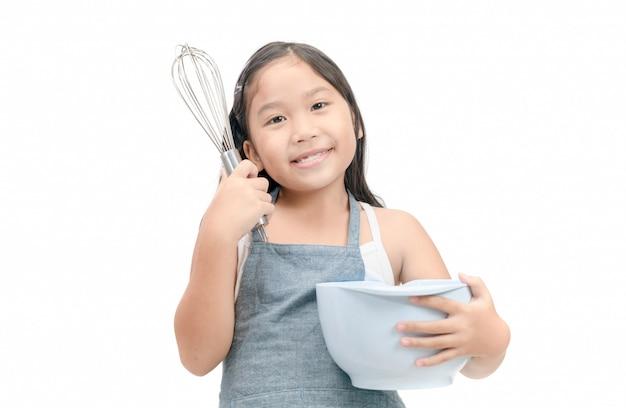 Linda garota asiática segurando utensílios de cozinha