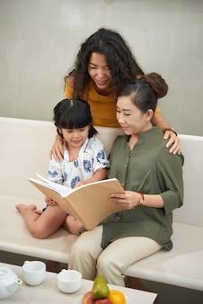 Linda garota asiática sentada no sofá, abraçada pela mãe e vendo fotos de livros com a mãe e a avó