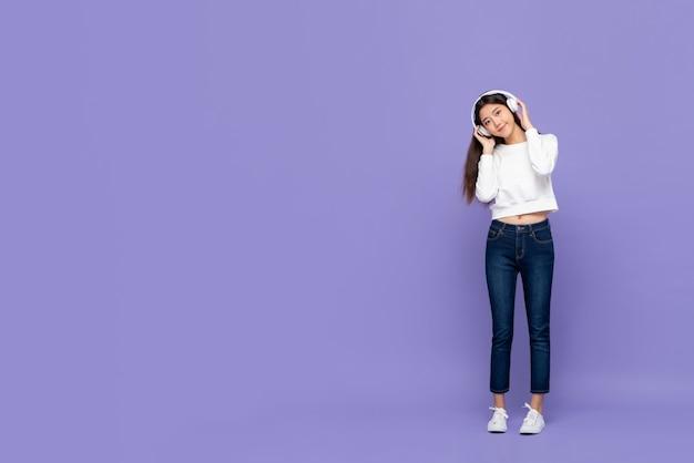 Linda garota asiática sorrindo e tocando fones de ouvido enquanto ouve música