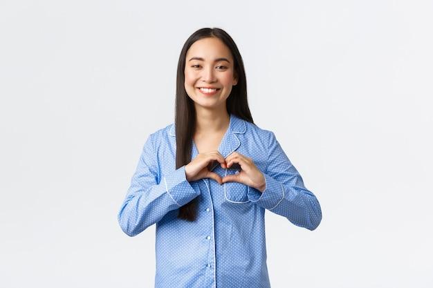 Linda garota asiática tenra em pijamas azuis, mostrando o gesto do coração e sorrindo, expressar amor e carinho, confessar simpatia, em pé de pijama, gostando de festa do pijama incrível, fundo branco.