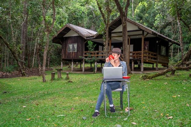 Linda garota asiática trabalhando e bebendo café na mesa em férias nas férias na natureza de colinas
