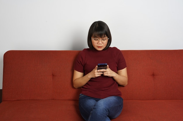 Linda garota asiática vestindo camisa vermelha e jeans azul sente-se no sofá segurando e usando o smartphone