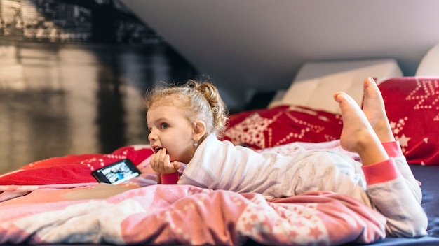 Linda garota assistindo vídeo na cama