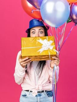 Linda garota assustada com chapéu de festa segurando balões e o rosto coberto com uma caixa de presente isolada na parede rosa
