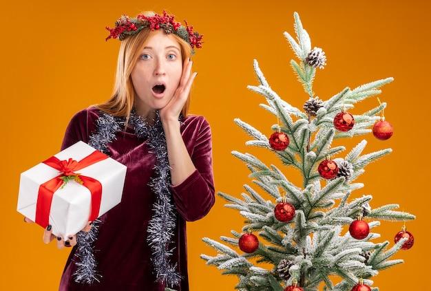 Linda garota assustada perto da árvore de natal usando vestido vermelho e grinalda com guirlanda no pescoço segurando uma caixa de presente e colocando a mão na bochecha isolada em fundo laranja