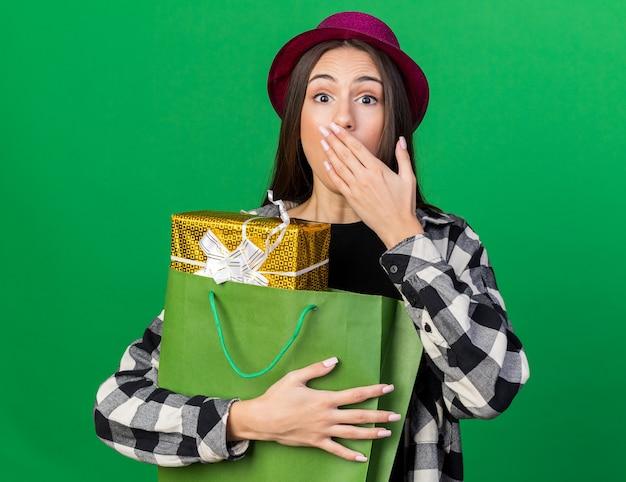 Linda garota assustada usando um chapéu de festa segurando uma sacola de presentes e tapando a boca com a mão