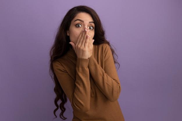 Linda garota assustada vestindo um suéter de gola alta marrom coberto com as mãos isoladas na parede roxa