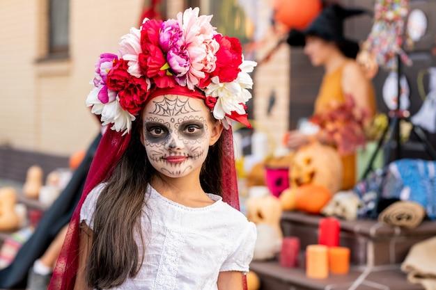 Linda garota assustadora com rosto pintado, olhando para você em pé na frente da câmera contra uma jovem de vestido amarelo e chapéu preto de bruxa