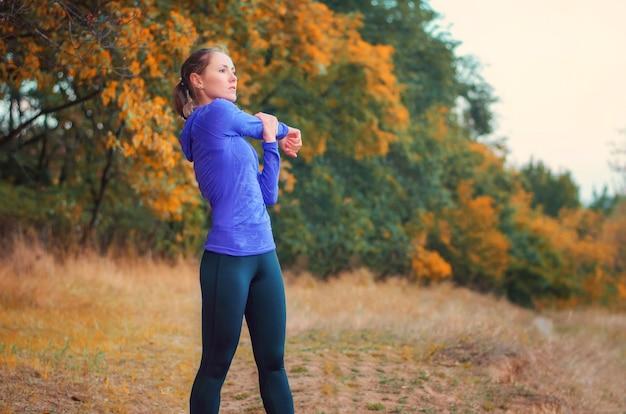 Linda garota atlética caucasiana com camisa azul e leggins esportivos pretos aquece antes de correr