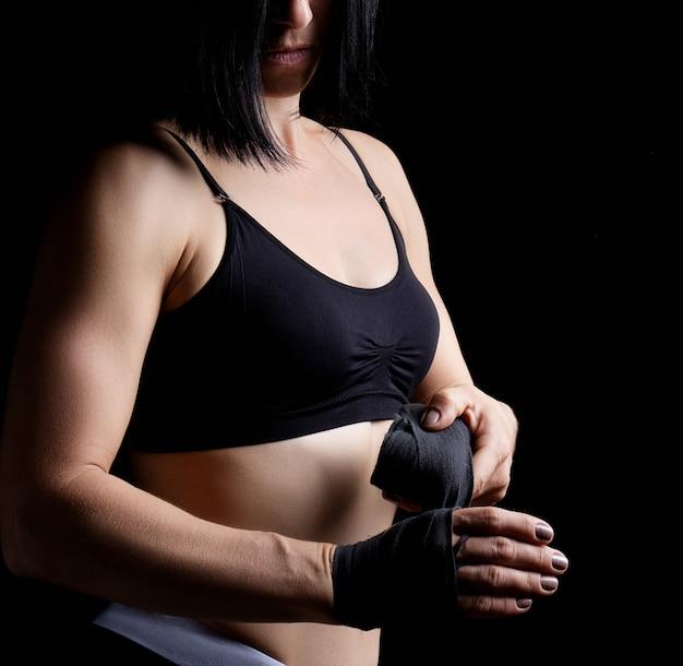 Linda garota atlética com cabelo preto rebobina a mão com uma bandagem elástica preta antes do treino