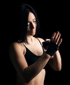 Linda garota atlética com cabelo preto rebobina a mão com uma bandagem elástica preta
