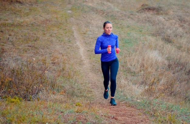 Linda garota atlética com camisa azul e leggins pretas com halteres rosa nas mãos dela corre ao longo do caminho montanhoso de outono.