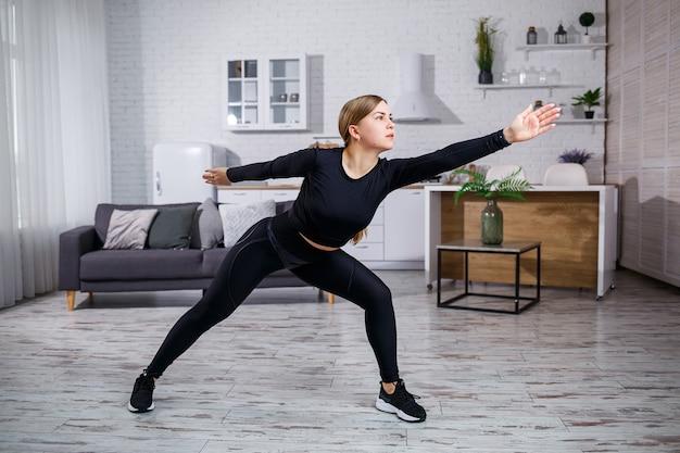 Linda garota atlética em uma legging e um top faz exercícios de alongamento. estilo de vida saudável. a mulher pratica esportes em casa.