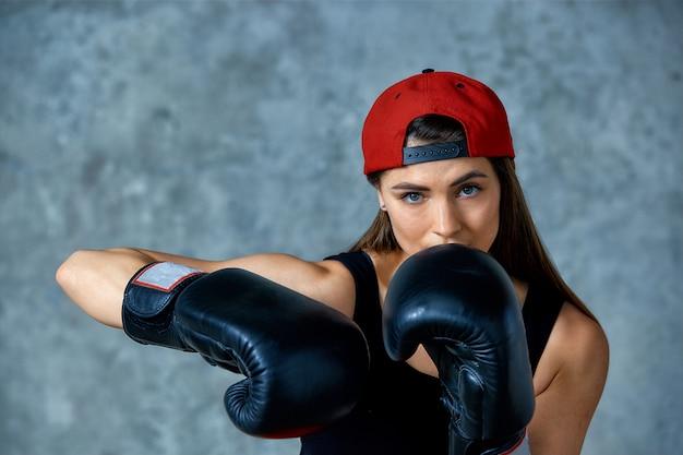 Linda garota atlética posando em luvas de boxe cor de rosa em um fundo cinza. copie o espaço. esporte de conceito, luta, realização do objetivo.
