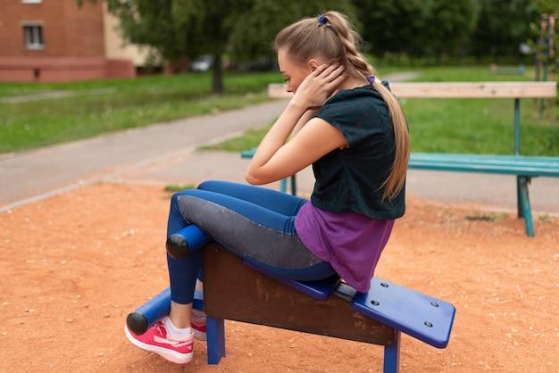 Linda garota atlética treina os músculos abdominais em um simulador de rua. para qualquer propósito
