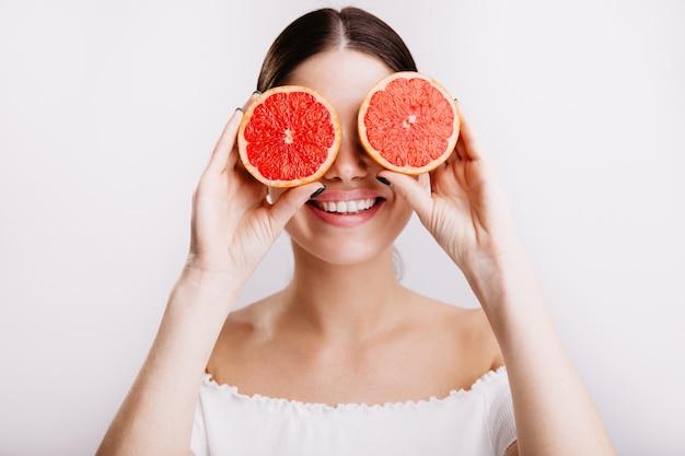 Linda garota atraente de cabelos escuros com poses de sorriso encantador, cobrindo os olhos com toranjas.