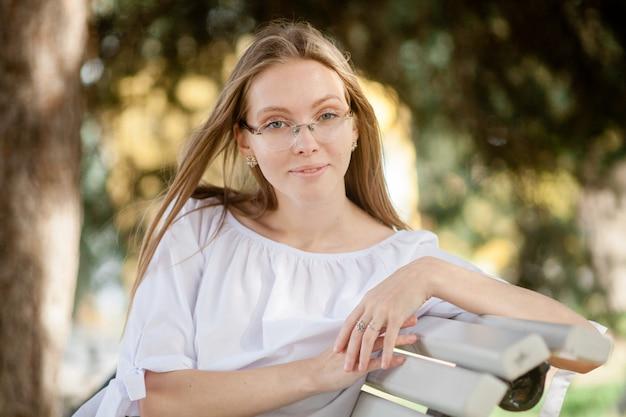 Linda garota atraente de óculos sentada no banco do parque de outono