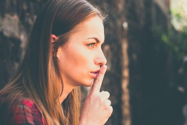 Linda garota atraente em cores vintage retrato cale a boca sinal para as pessoas - expressão irritada para jovem mulher caucasiana